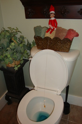 elf on the shelf fishing in the toilet